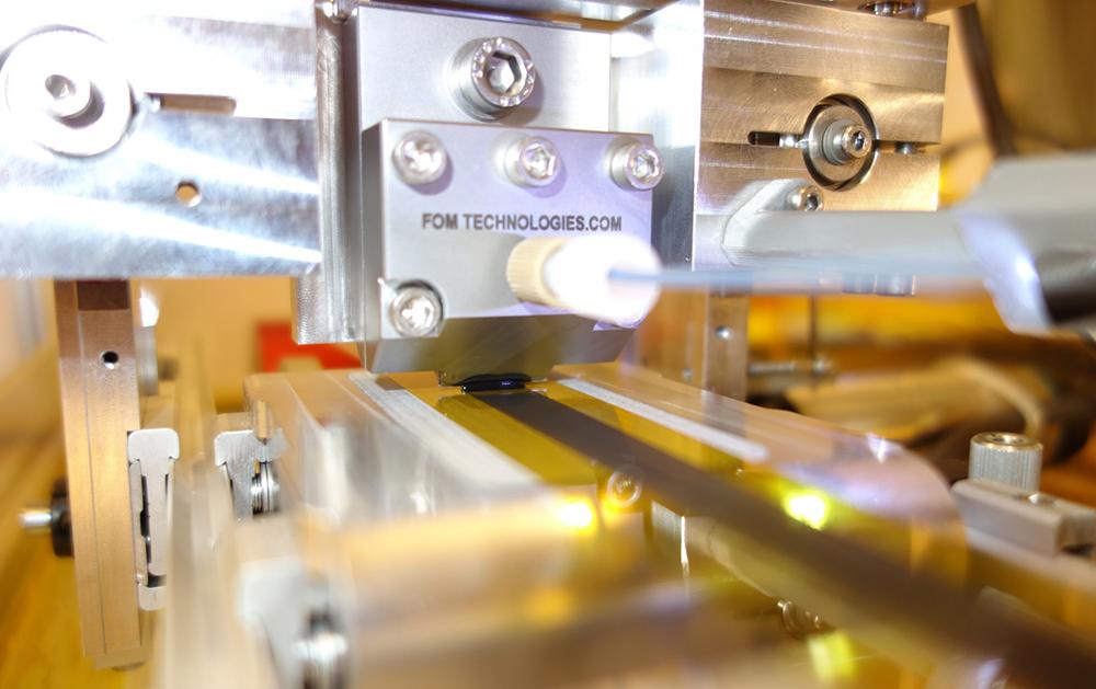 in-FORM-maskinen. På bilden ses bläckblandningen appliceras på det rörliga bandet.